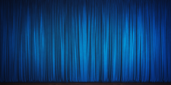 Blue velvet theater curtain. Blue velvet curtain is contacting wood ground. Panoramic composition.