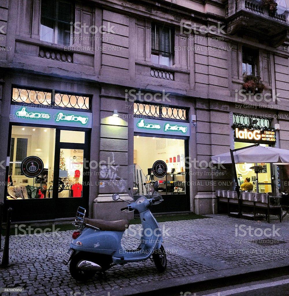 Blue Vespa parked on Milan street stock photo