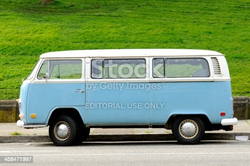 San Francisco, United States - March 26, 2012: A vintage, blue Volkswagen Bus is parked next to a hill covered in bright green grass at the Alamo Square Park.