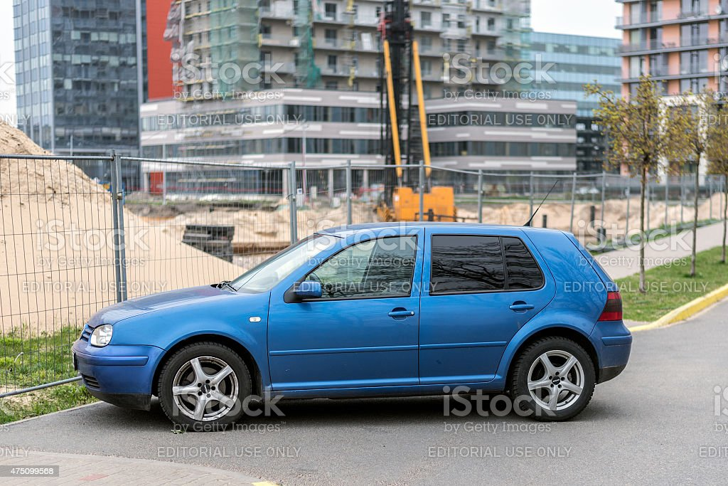 Blue Volkswagen Golf IV parked near construction site stock photo