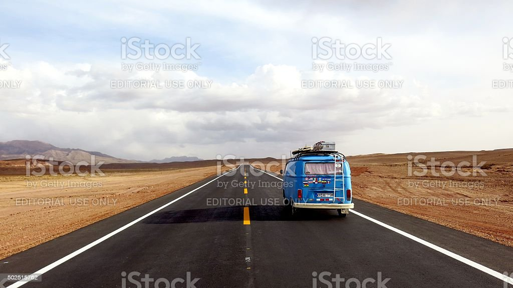Blue VW Bus driving on new road on Altiplano, Bolivia stock photo