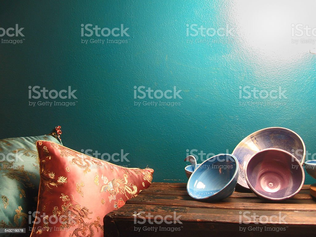 Blue wall with silk pillows and ceramic bowls stock photo