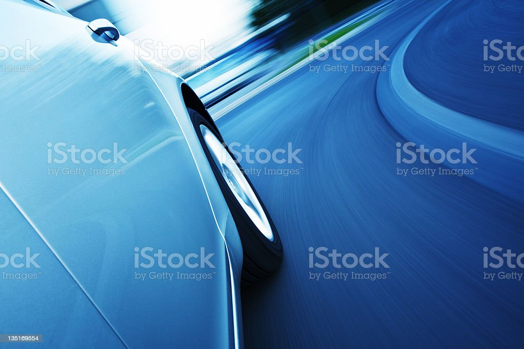 Blue washed motion photo of a car turning a curve in a road royalty-free stock photo
