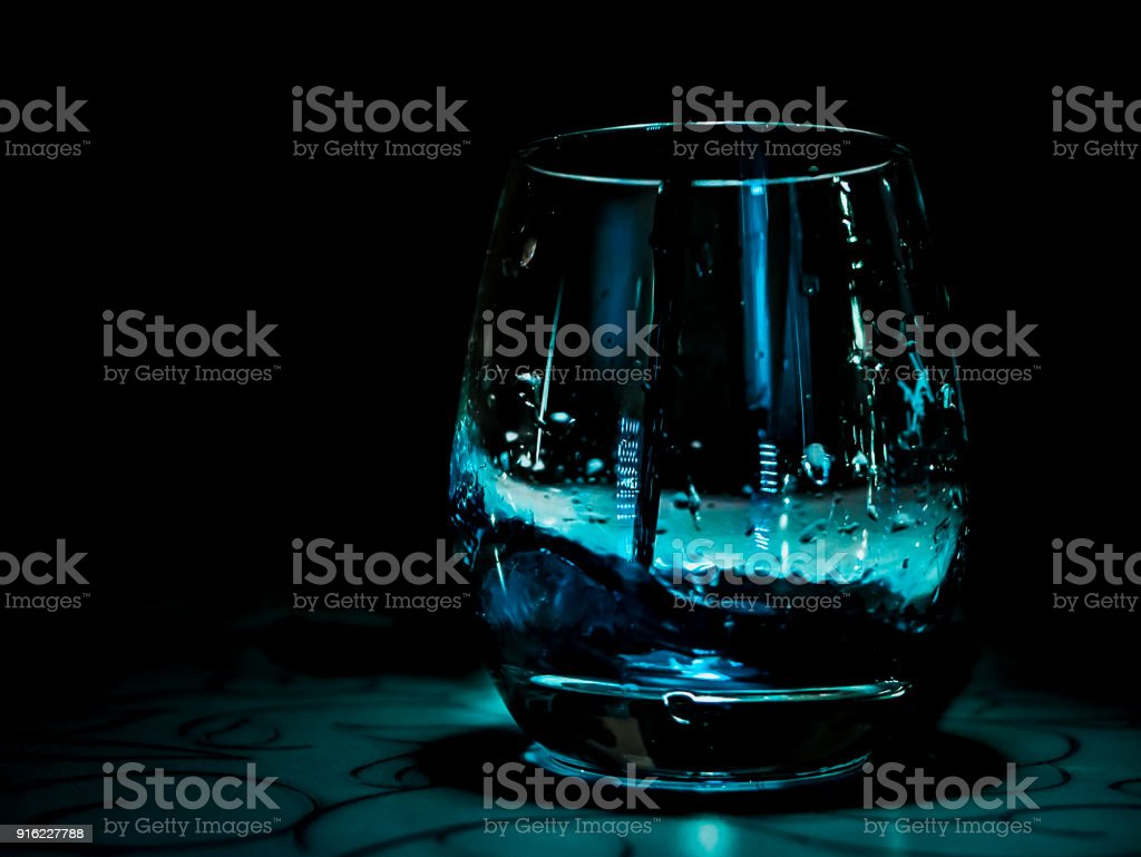 blue water drop into the glass on the table, black background
