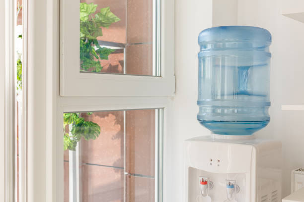 blue water gallon on electric water cooler in office area blue water gallon on electric water cooler in office area cooler container stock pictures, royalty-free photos & images
