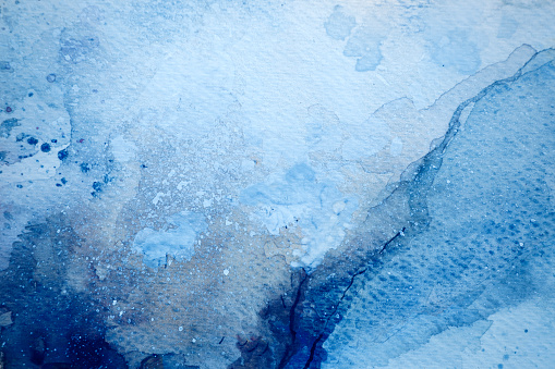 Abstract wet blue watercolor background on white watercolor paper. My own work.