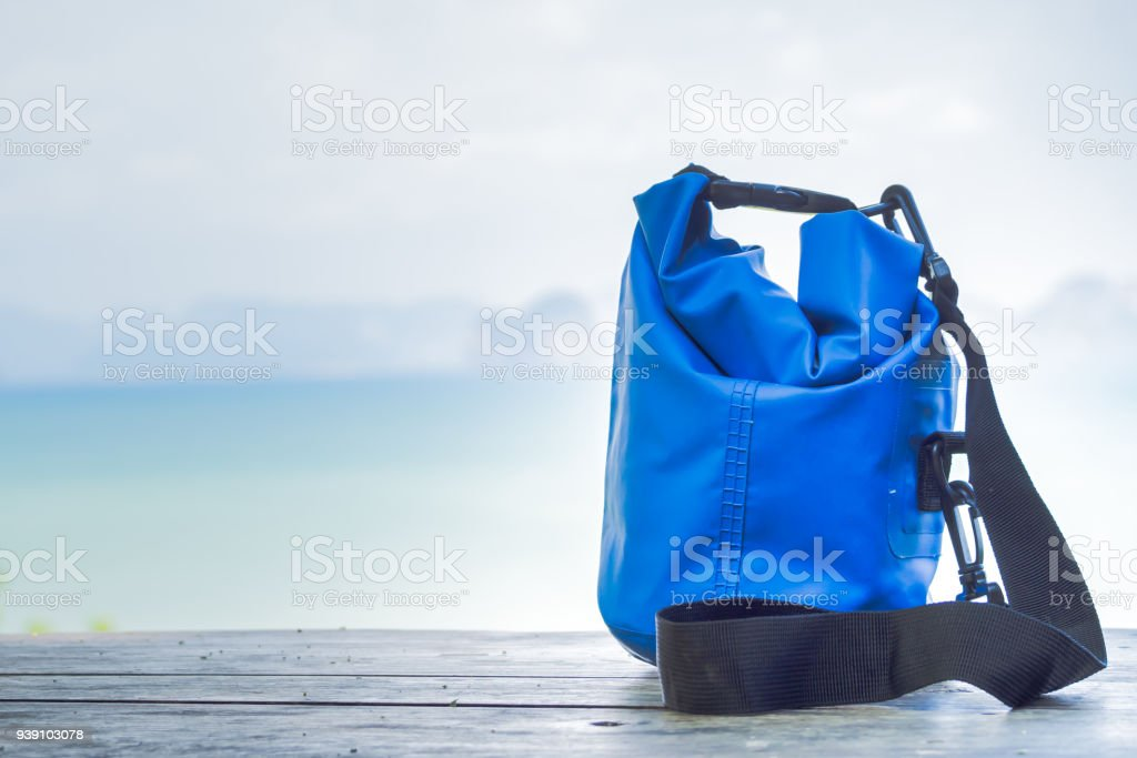 Blue waterproof bag on wooden table with blurry seascape background. stock photo