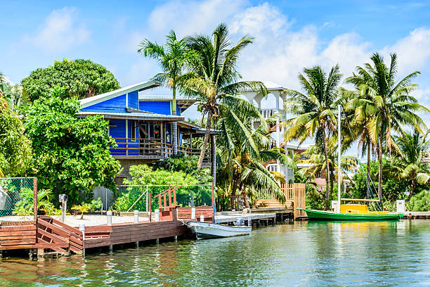 Blue waterside house & boats, Placencia, Belize, stock photo