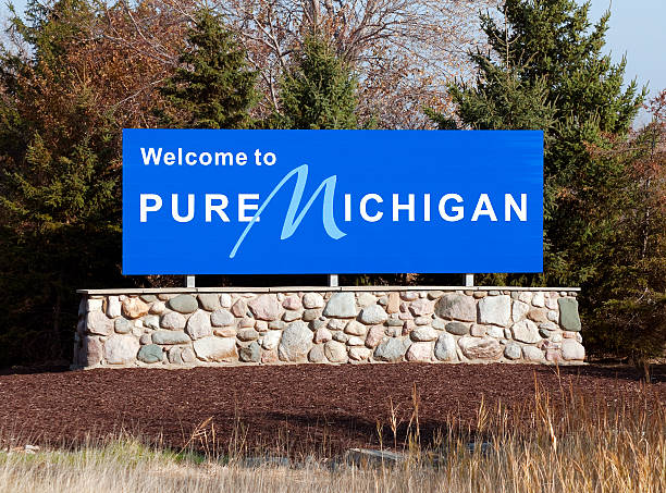 Blue welcome to pure michigan sign on a stone wall A welcome sign at the Michigan state line. ann arbor stock pictures, royalty-free photos & images