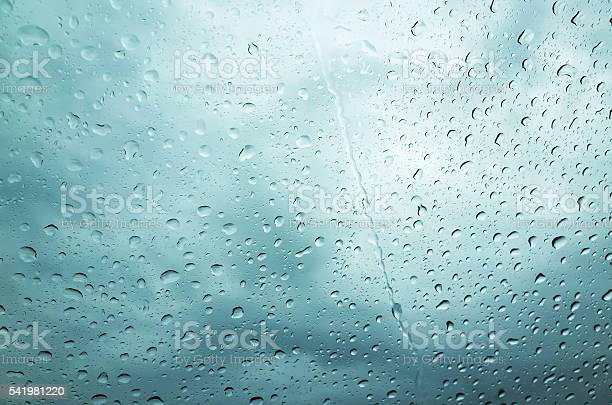 Photo of Blue wet glass with droplets, rainy background