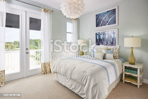 A large bed sits next to a double door leading out to a small balcony overlooking a sandy seascape. The wall is a blue gray color, and the doors and windows are white. The curtains are see through with fringe orange and blue patterning. On the ceiling is an interesting chandelier of white overlapping cups, creating a flower effect. On the wall above the bed hangs two photos of back, black bicycle tires, blue tire guards, and red, oval reflectors. Below, on the bed, sits two long white pillows, two pillows matching the drapery, and three pillows matching the white, light blue, and tan bed spread. On the four leaf clover, sandy white end tables sits a yellow lamp with a twist in its neck and a white lamp shade. Three books of various sizes and colors are on the end table in shot. The floor is a brown carpet.