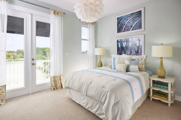 A Blue, White, and Off-White, Bedroom with a Bicycle Theme in a Model Home A large bed sits next to a double door leading out to a small balcony overlooking a sandy seascape. The wall is a blue gray color, and the doors and windows are white. The curtains are see through with fringe orange and blue patterning. On the ceiling is an interesting chandelier of white overlapping cups, creating a flower effect. On the wall above the bed hangs two photos of back, black bicycle tires, blue tire guards, and red, oval reflectors. Below, on the bed, sits two long white pillows, two pillows matching the drapery, and three pillows matching the white, light blue, and tan bed spread. On the four leaf clover, sandy white end tables sits a yellow lamp with a twist in its neck and a white lamp shade. Three books of various sizes and colors are on the end table in shot. The floor is a brown carpet. bedroom stock pictures, royalty-free photos & images