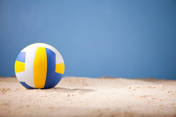 Blue white and yellow volleyball on beach with copy space stock photo