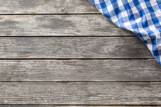 Blue white checketed tablecloth on wooden kitchen table - top of view stock photo