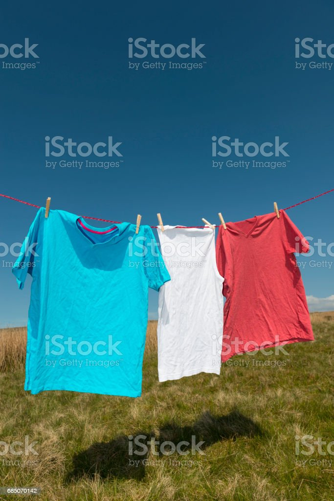 Blue, white, red T-shirts on a washing line. stock photo