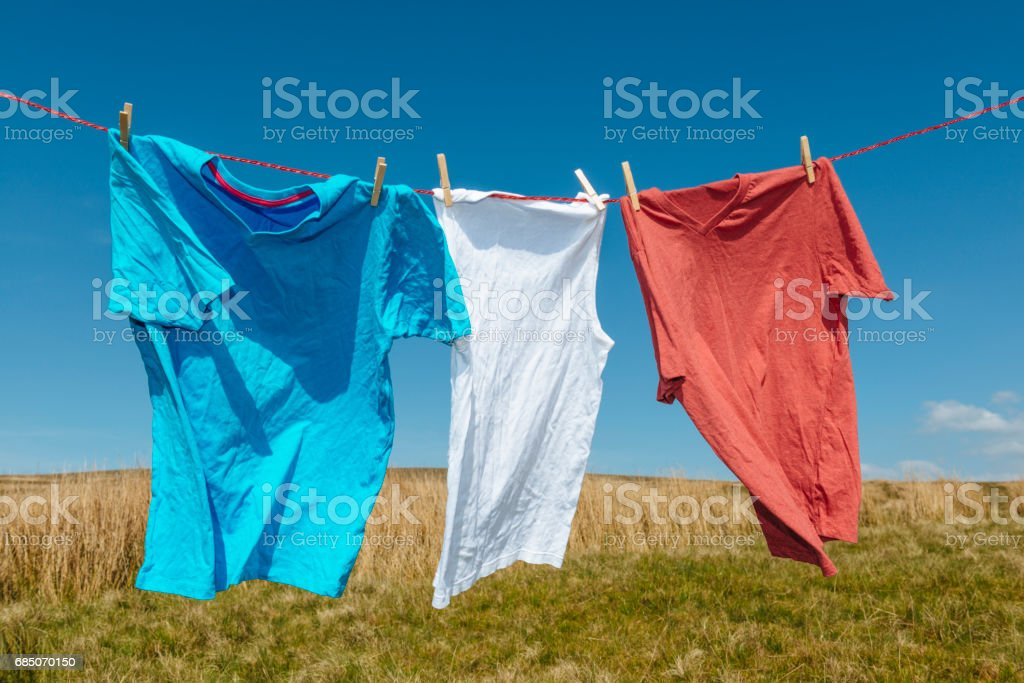 Blue, white, red T-shirts on a washing line. royalty-free stock photo