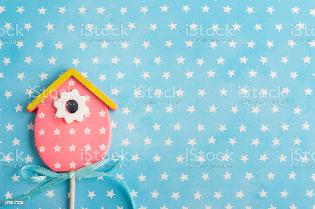 Blue white stars background with pink bird house stock photo
