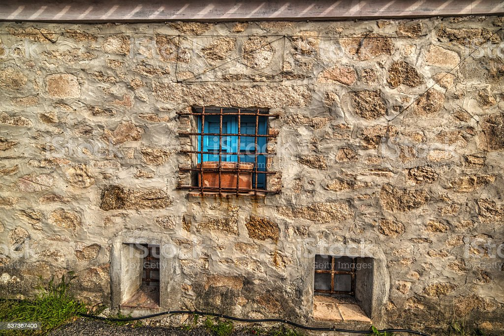 blue window in a rustic wall stock photo