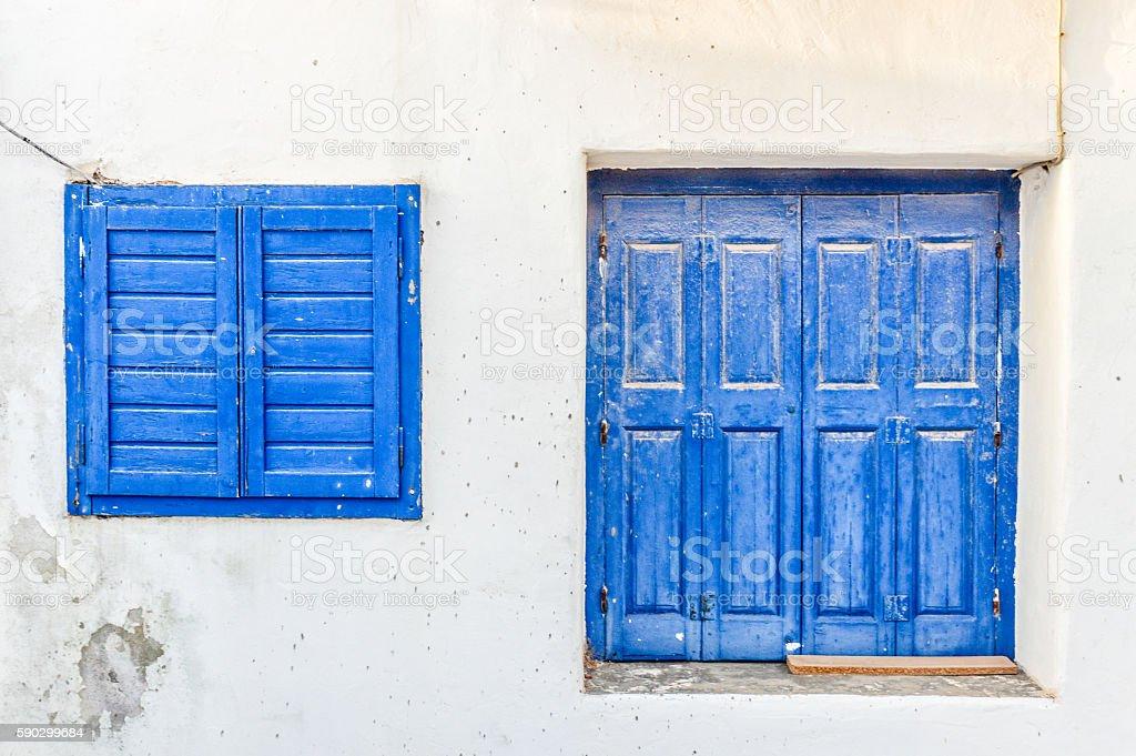 Blue windows and shutters on white buildings - Greece royaltyfri bildbanksbilder