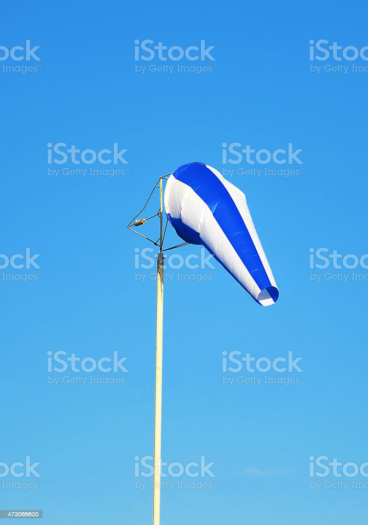 Blue windsock against sky background. stock photo