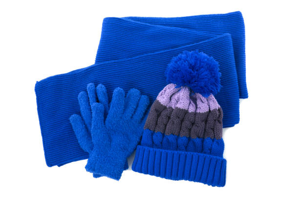 Blue winter knitted bobble hat, scarf gloves isolated stock photo