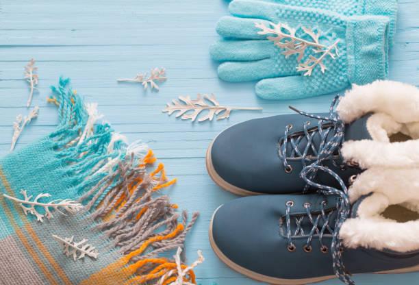 blaue winterschuhe und handschuhe auf blauem hintergrund aus holz - damenschuhe k stock-fotos und bilder