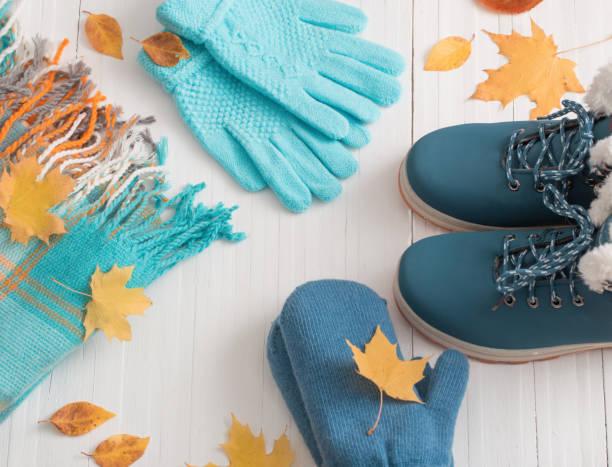 blaue winterschuhe und handschuhe auf weißem holz hintergrund - kinder winterstiefel stock-fotos und bilder