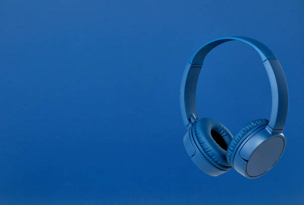 Blue wireless headphones on blue background stock photo