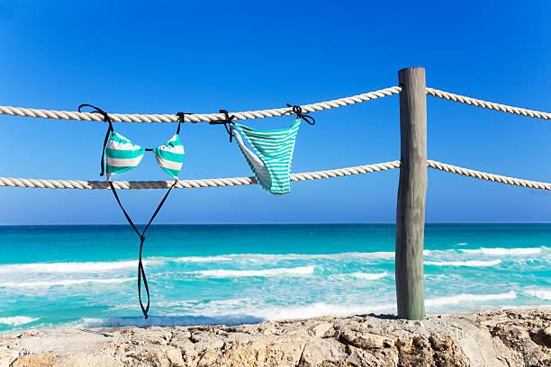 blau frau badekleidung hängen am seil weiß - horizontal gestreiften vorhängen stock-fotos und bilder