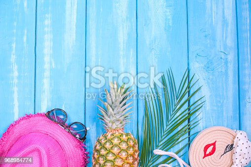 674650538istockphoto Blue wood background, pineapple, pink hat, palm branch, sunglasses, place for text in the center. Accessories for the beach and holidays. Copy space, flat lay 968984774