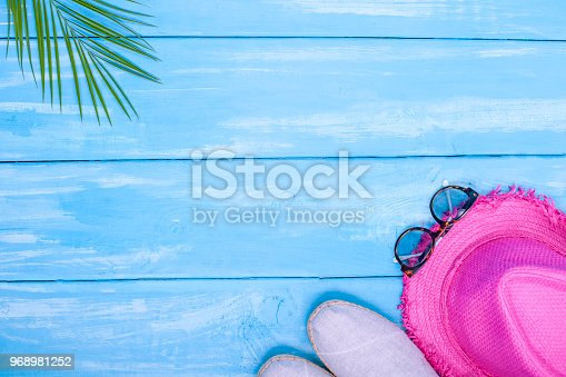 674650538istockphoto Blue wooden background, shoes, pineapple, pink hat, palm branch, sunglasses, place for text in the center. Accessories for the beach and holidays. Copy space, flat lay 968981252