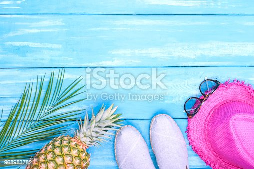 674650538istockphoto Blue wooden background, shoes, pineapple, pink hat, palm branch, sunglasses, place for text in the center. Accessories for the beach and holidays. Copy space, flat lay 968983782