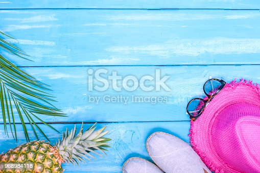 674650538istockphoto Blue wooden background, shoes, pineapple, pink hat, palm branch, sunglasses, place for text in the center. Accessories for the beach and holidays. Copy space, flat lay 968984118