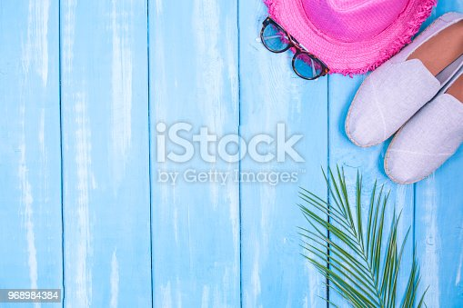 674650538istockphoto Blue wooden background, shoes, pineapple, pink hat, palm branch, sunglasses, place for text in the center. Accessories for the beach and holidays. Copy space, flat lay 968984384