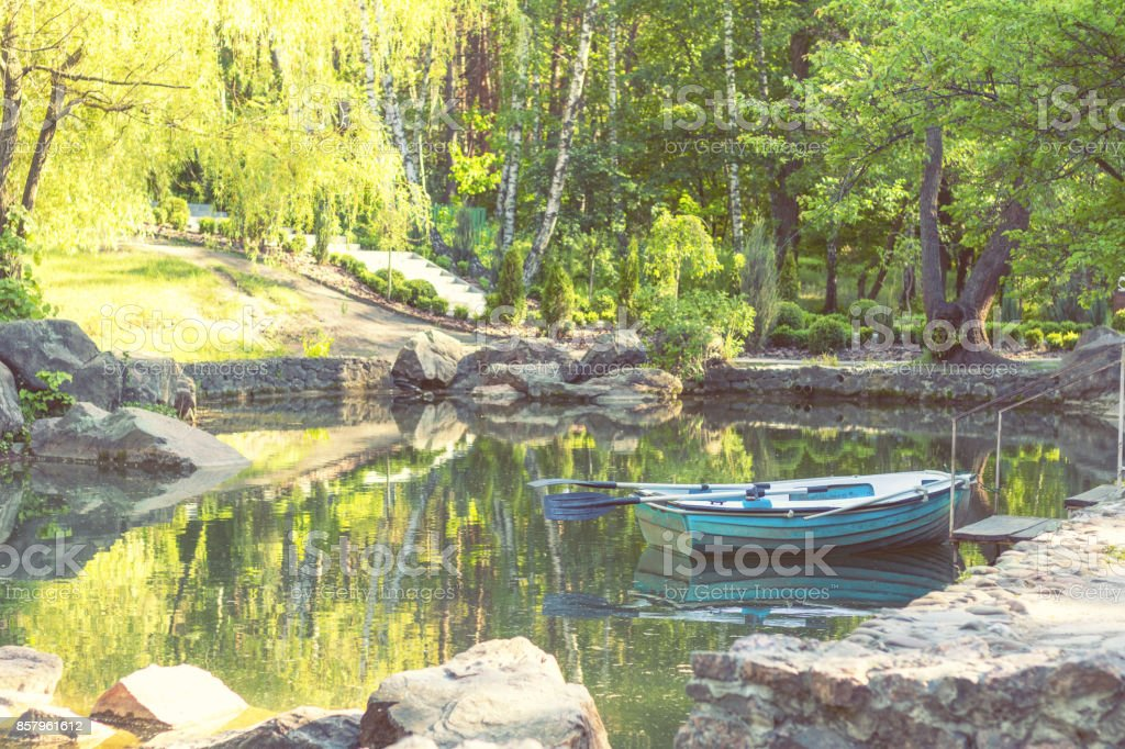 Blue wooden boat in the park pond on a sunny day stock photo