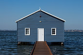 Blue wooden boatshed surrounded by water against clear blue sky