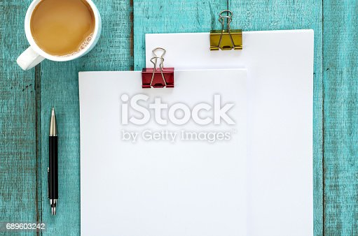 istock Blue wooden desk table with paper reams and cup of coffee. Top view with copy space, flat lay. 689603242