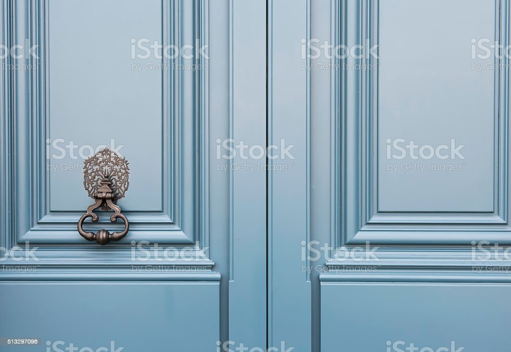 Blue wooden door with an old knocker knob stock photo