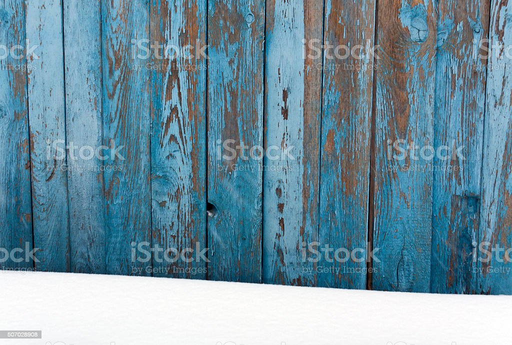 Blue wooden fence in snow. stock photo