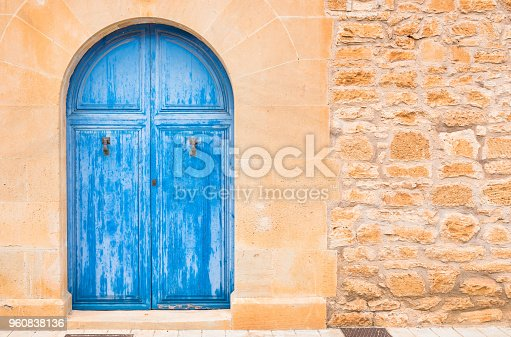 Detail view of mediterranean house blue wooden door and stone wall background