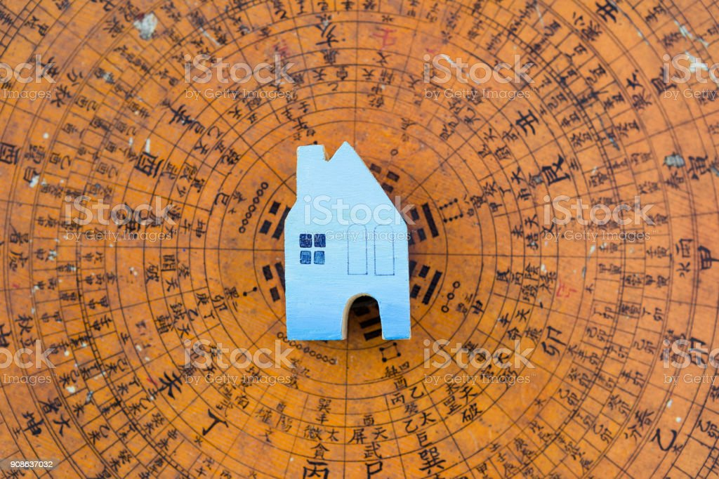 Blue wooden miniature house on blurred ancient feng shui compass stock photo