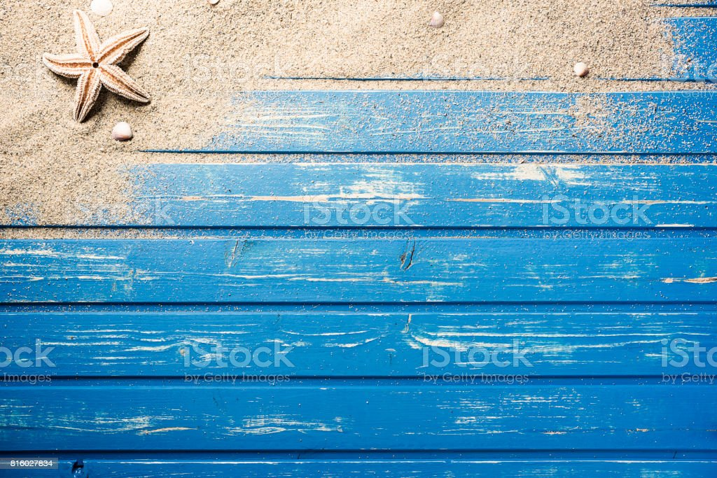 Blauwe houten vlonder met strand zand foto
