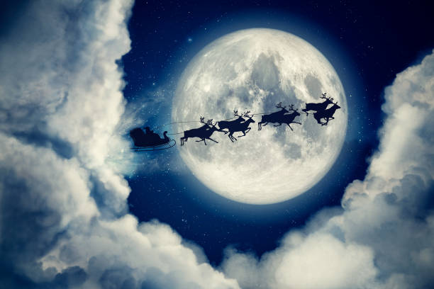 Blue xmas eve night with moon and clouds with Santa Claus sleight and reindeer silhouette flying to bring gifts and presents with text space to place logo or copy. Christmas present greeting post card Blue xmas eve night with moon and clouds with Santa Claus sleight and reindeer silhouette flying to bring gifts and presents with text space to place logo or copy. Christmas present greeting post card. sleigh stock pictures, royalty-free photos & images