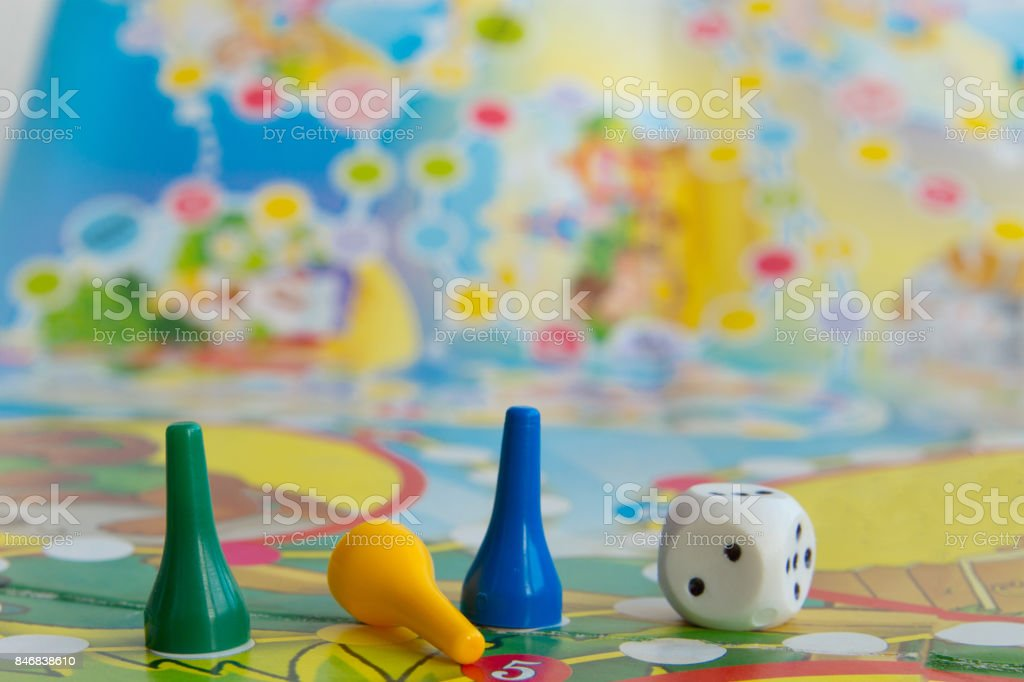 Chips de plástico azul, amarelo e verde, dados e jogos de tabuleiro para crianças.  foco seletivo - foto de acervo