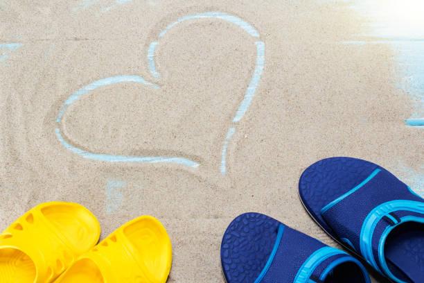 blau, gelb flip flops und herz am sandstrand. - flitterwochen flip flops stock-fotos und bilder