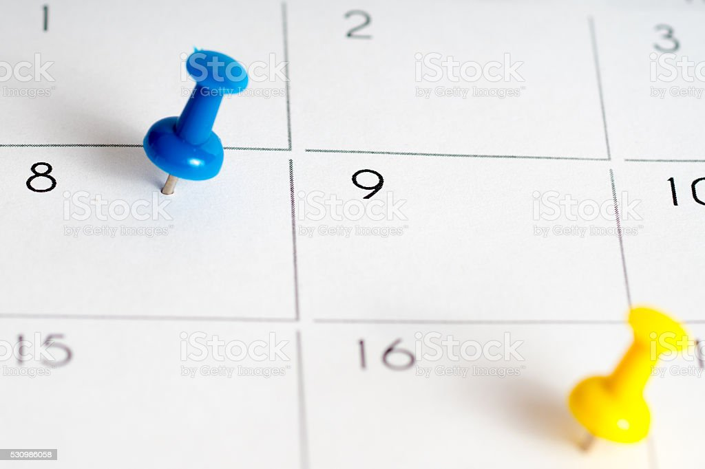 blue yellow pins on calendar grid stock photo