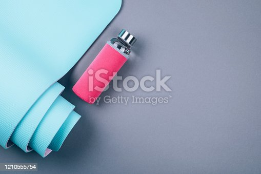 637596492 istock photo Blue yoga mat and glass water bottle on grey background. 1210555754