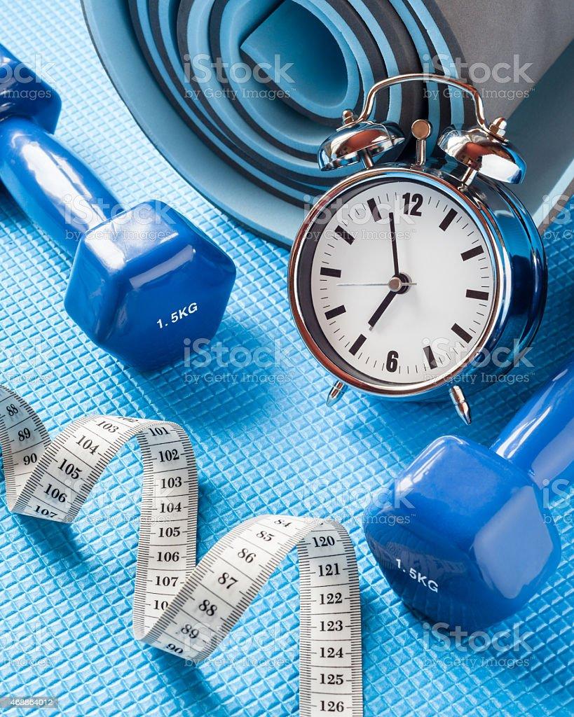 Blue yoga mat, two dumbbells, tape measure and alarm clock. stock photo