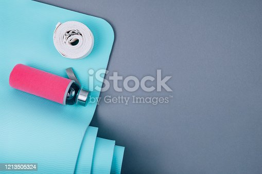 637596492 istock photo Blue yoga mat, white belt and glass water bottle on grey background. 1213505324