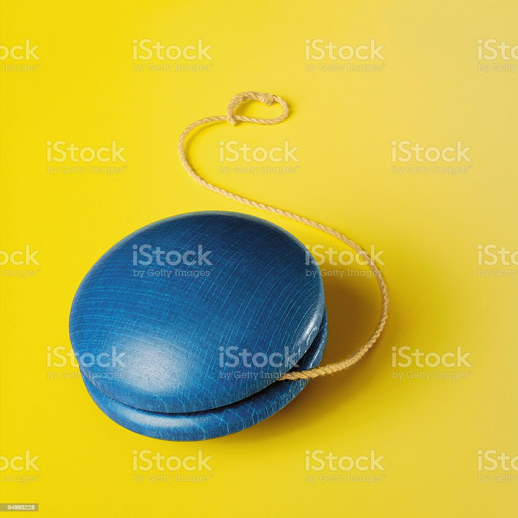 Blue yo-yo on yellow background royalty-free stock photo